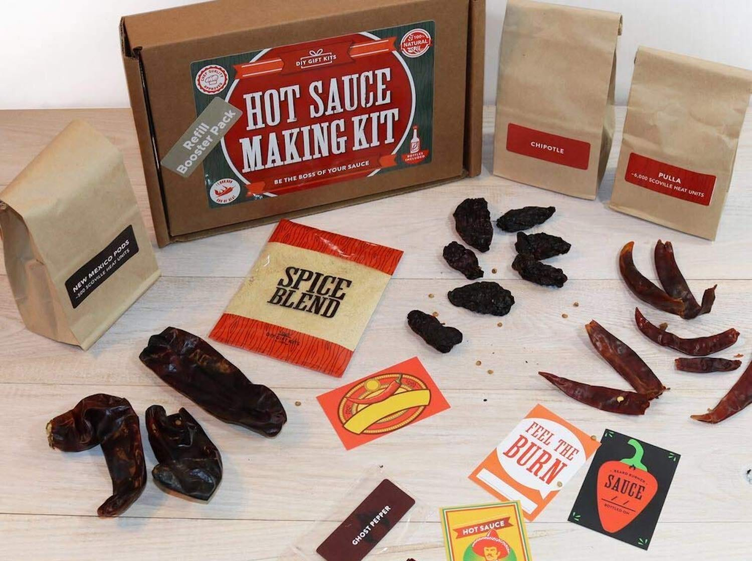 """A brown box labeled """"Hot Sauce Making Kit"""" with assorted peppers and spice blend envelopes sitting on the table nearby"""