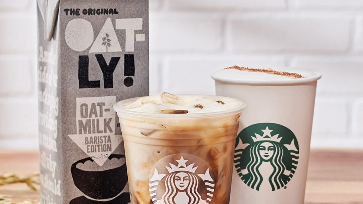 A container of Oatly oat milk sits behind two Starbucks drinks.