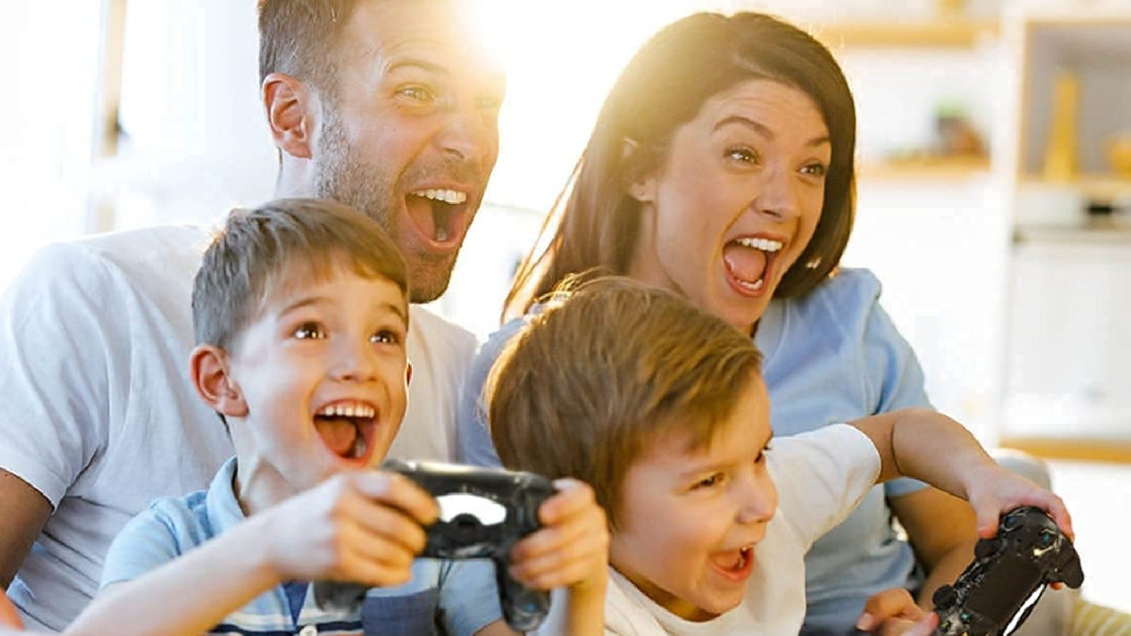 A family smiles at a video game while the young boys hold the controllers.