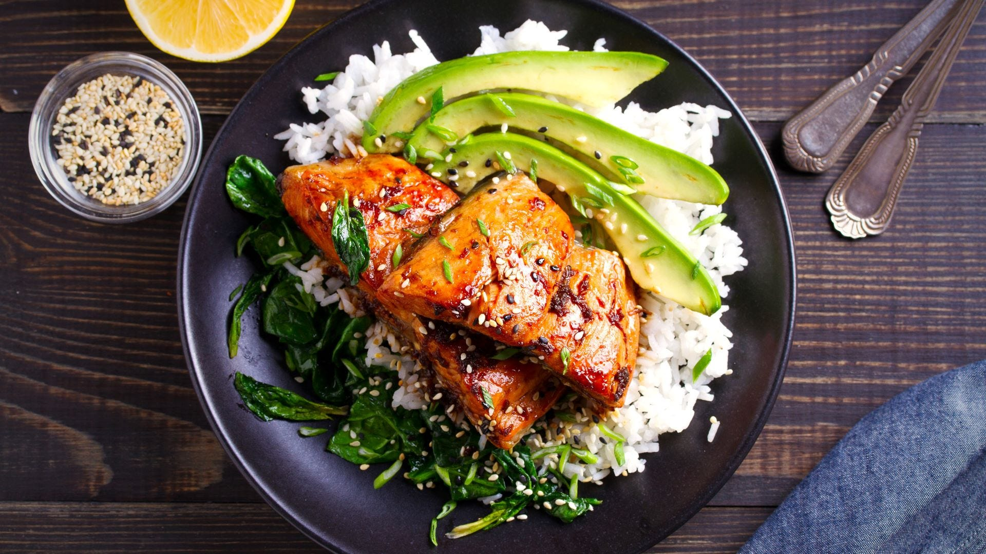 A plate of salmon in honey-soy glaze with rice, spinach, and avocado.