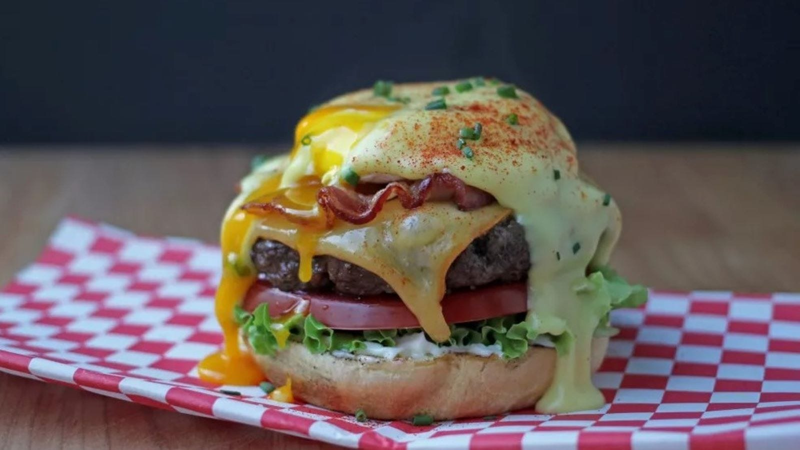 A brunch burger sitting on red-and-white checked paper.