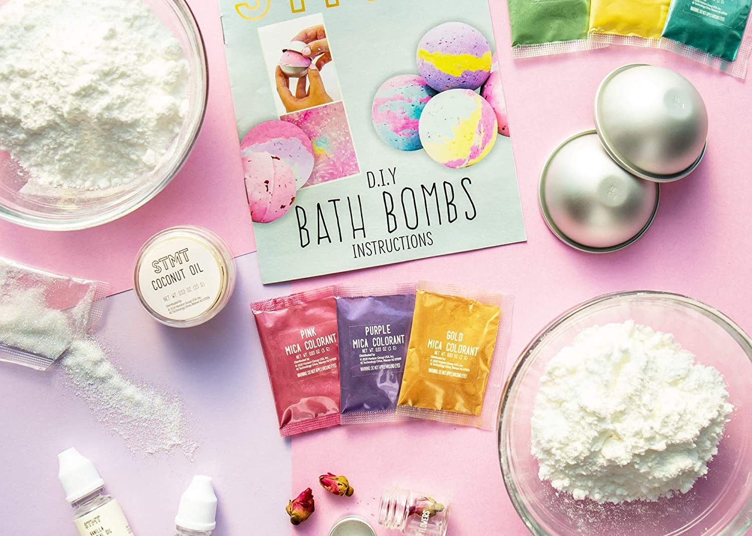 Materials for bath bombs (vials of oil, different powders, etc.) on a colorful surface