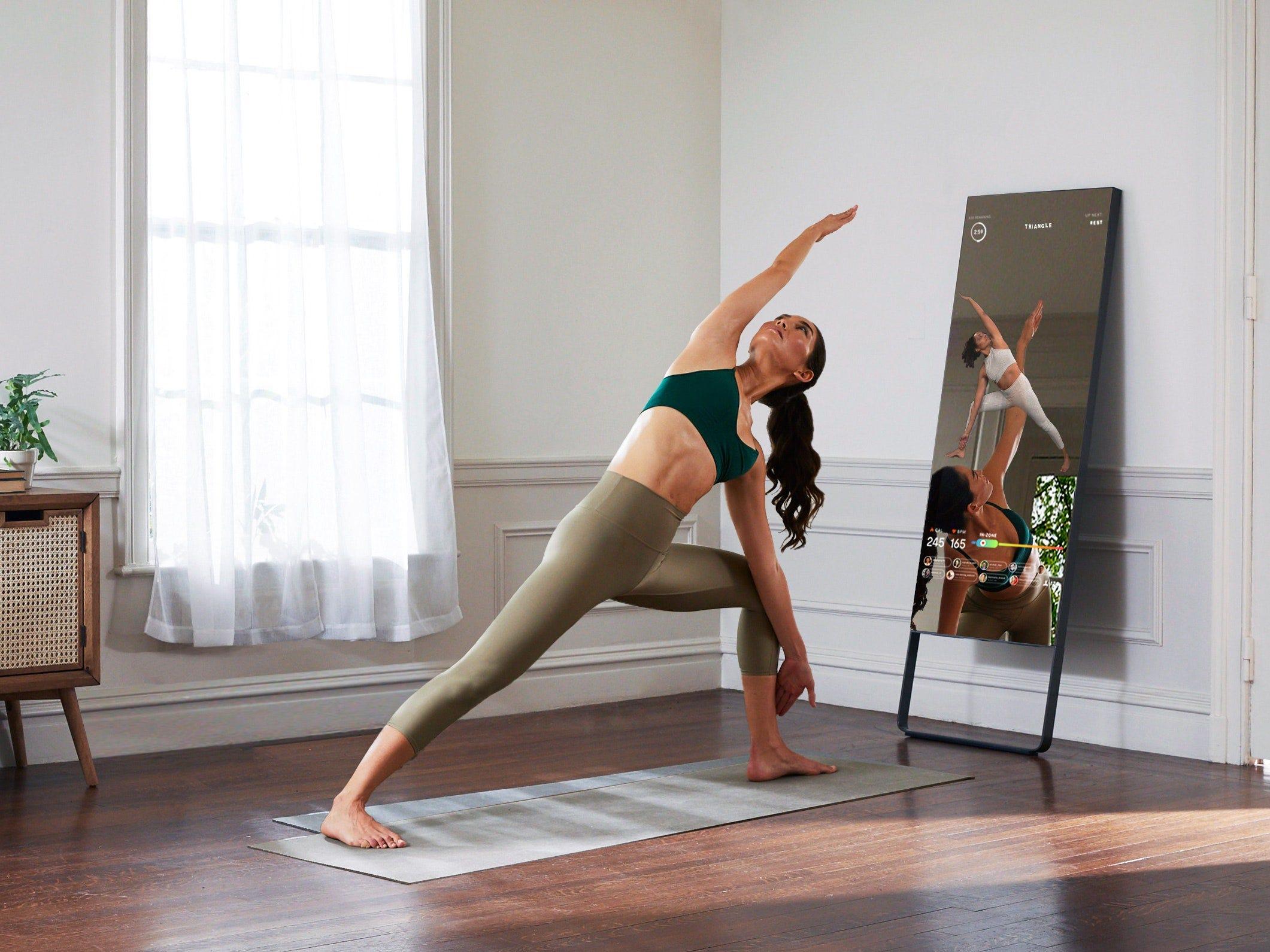 Женщина занимается йогой перед домашним фитнес-центром Mirror.