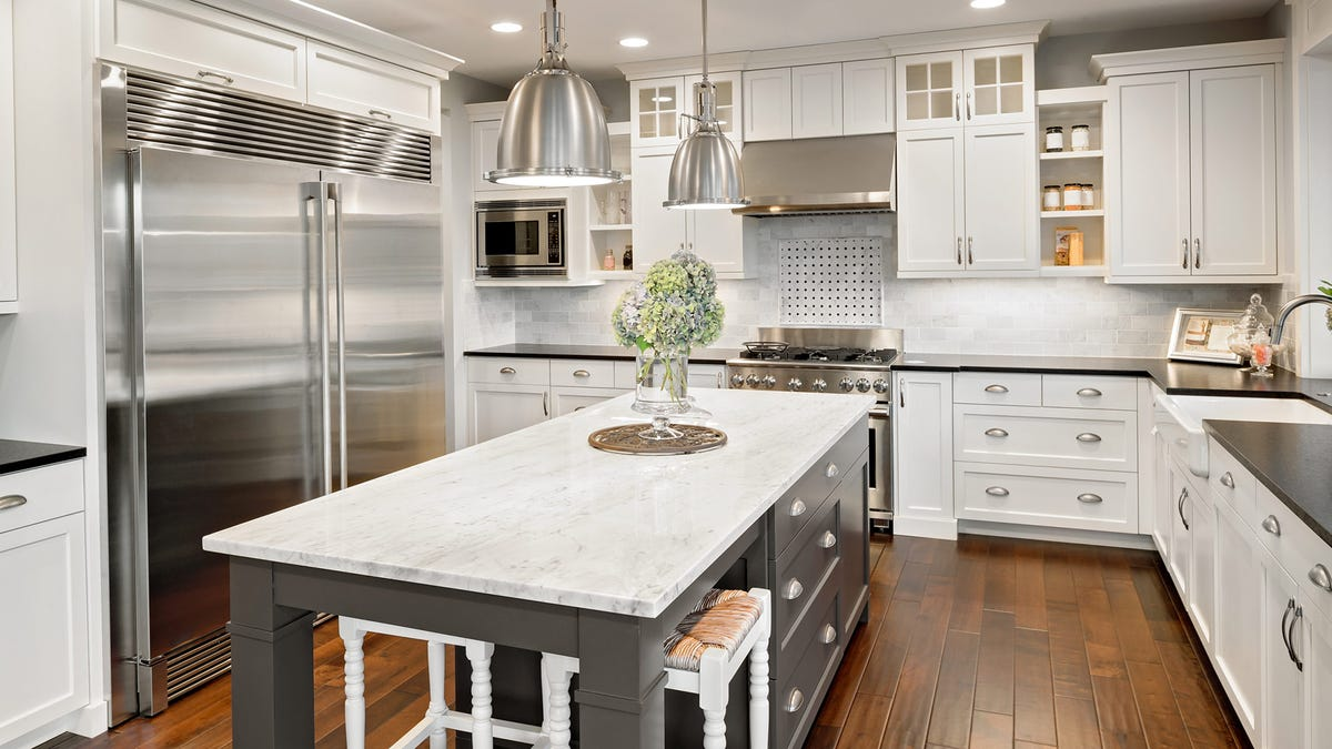 A brightly light kitchen with a stainless steel refrigerator.