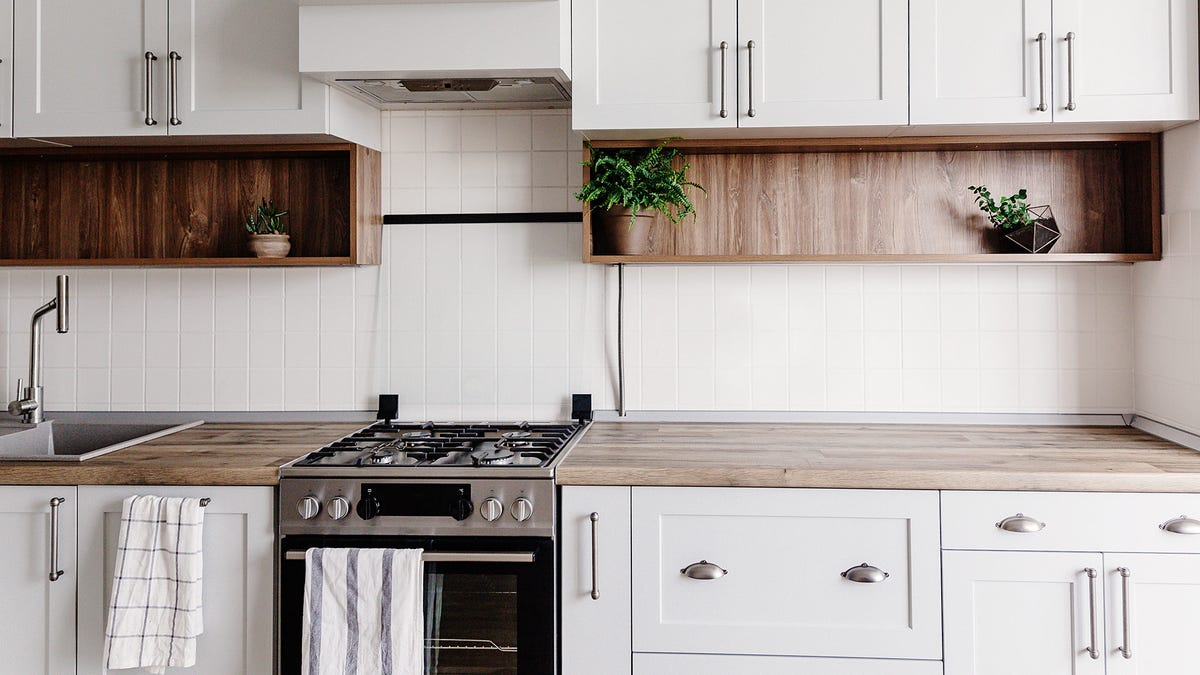 A sunny kitchen with oak counters, white cabinets, and a white tile backsplash.
