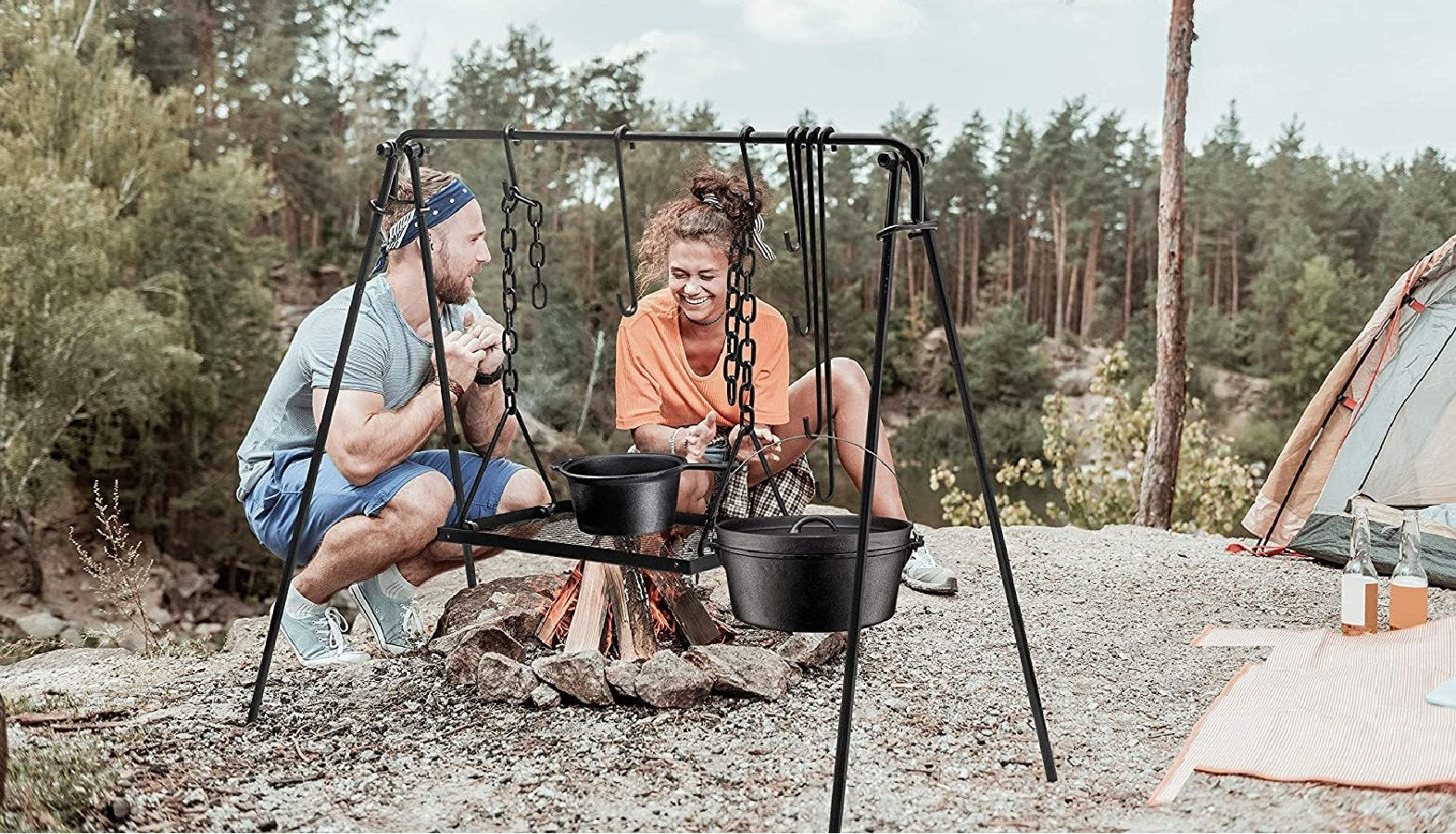 A couple chatting together at camp, while their food simmers away on a Bruntmor campfire grill swing.
