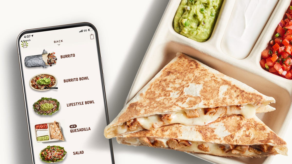 A Chipotle quesadilla sitting on a tray next to a phone displaying the menu in the Chipotle app.