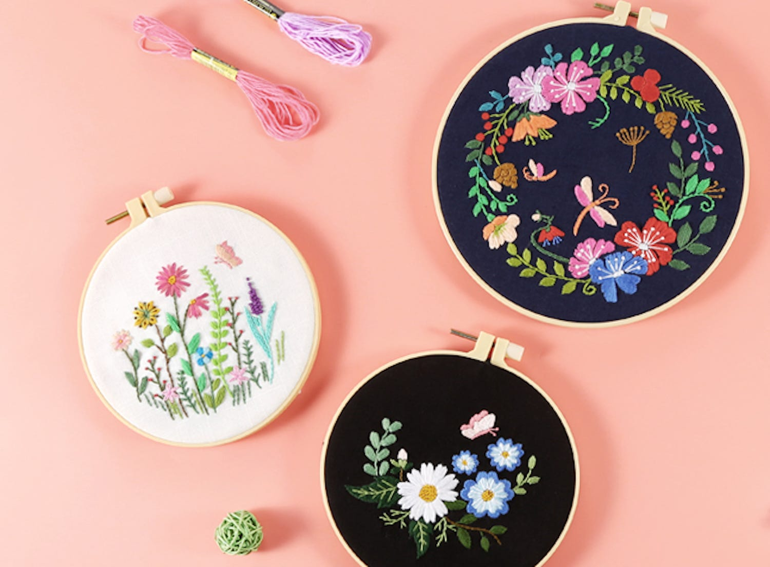 Three embroidery hoops holding fabric embroidered with floral designs