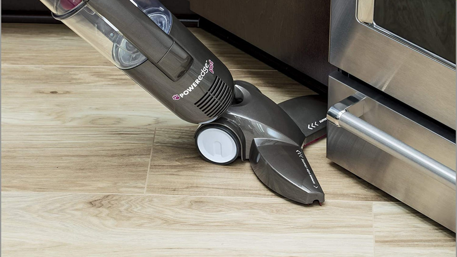 Someone using the Bissell PowerEdge Pet Vacuum on a hardwood kitchen floor.