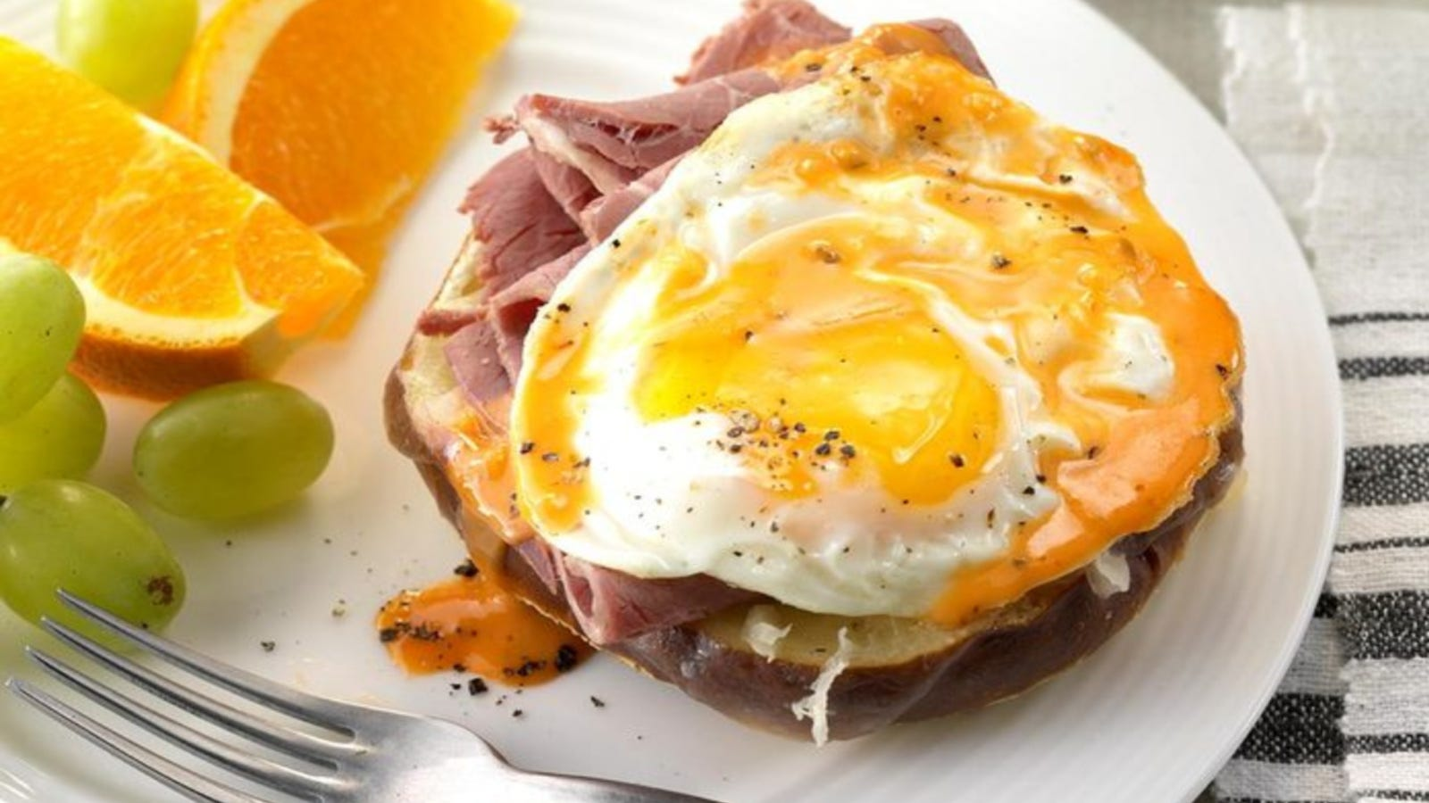 A fried egg on top of sliced corned beef on a pretzel roll, topped with a drizzle of Russian dressing with a side of grapes and organges.