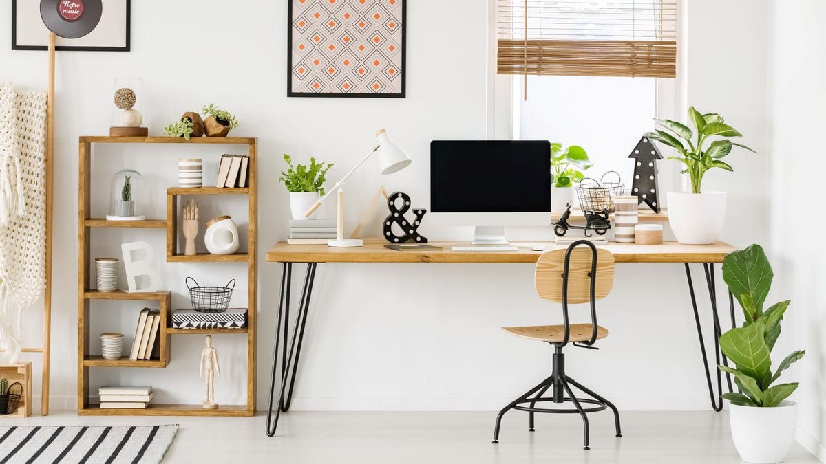 A Scandi design home office with white walls, a wooden desk, chair, and shelves, and several plants.