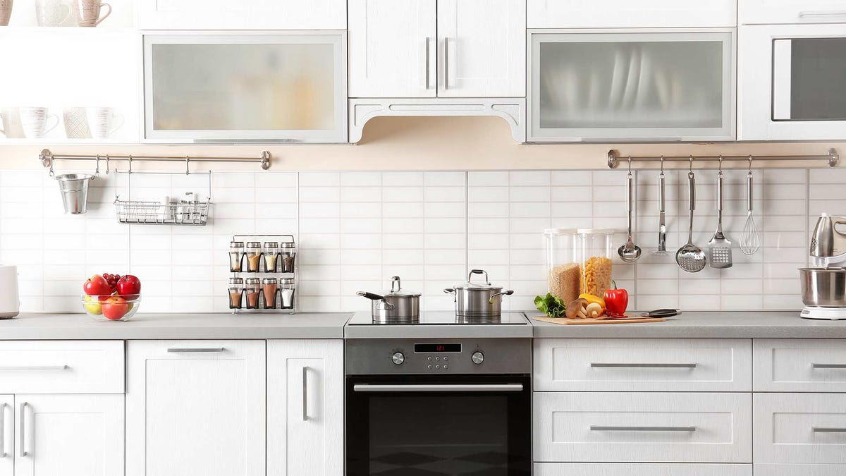 A sunny kitchen with white cabinets and items placed on the counters.
