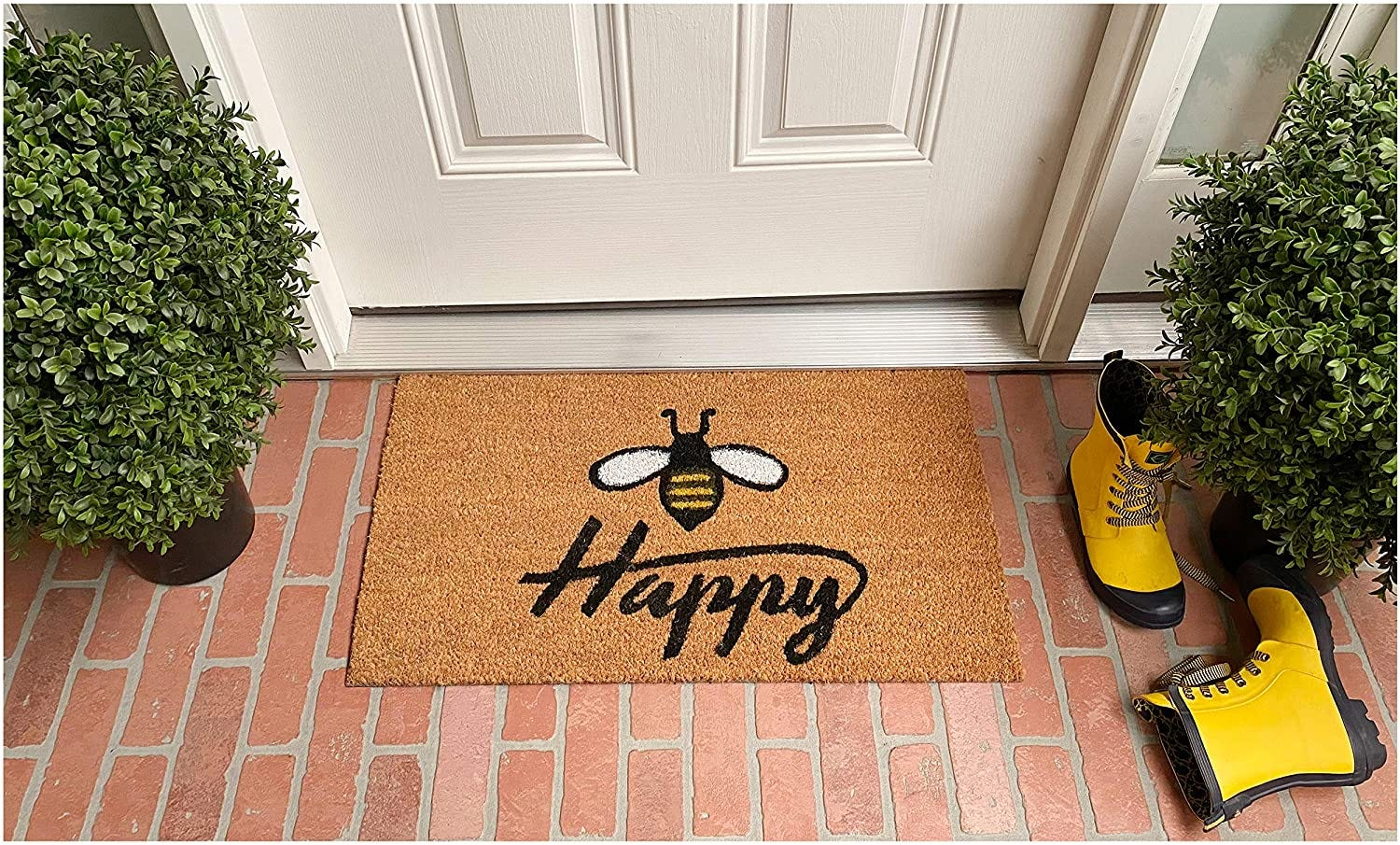 """A doormat with a bee design above the word """"happy"""", on a brick patio in front of a white door"""