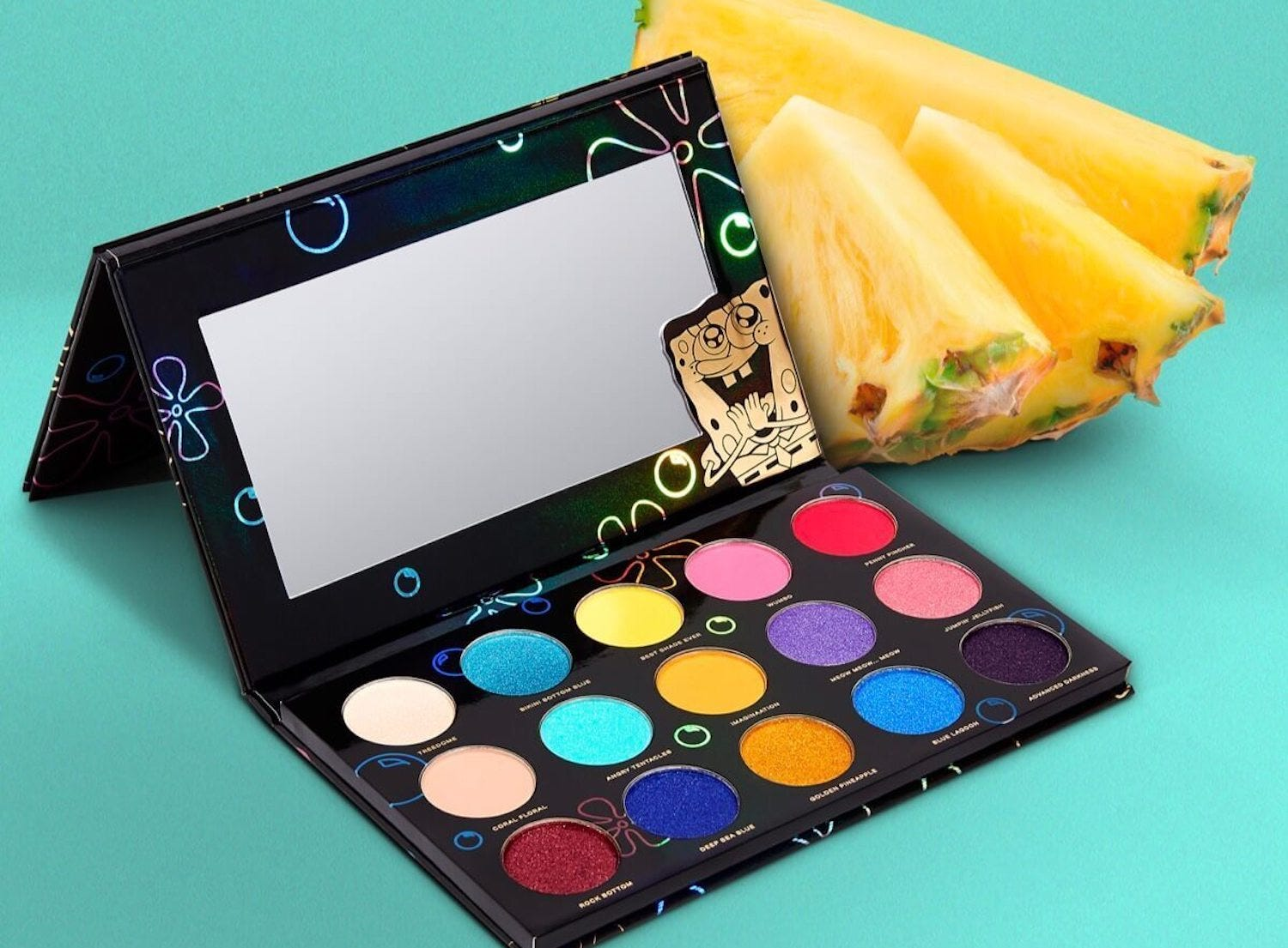 An open makeup palette with a rainbow of eyeshadows and a small mirror, next to a few pineapple slices