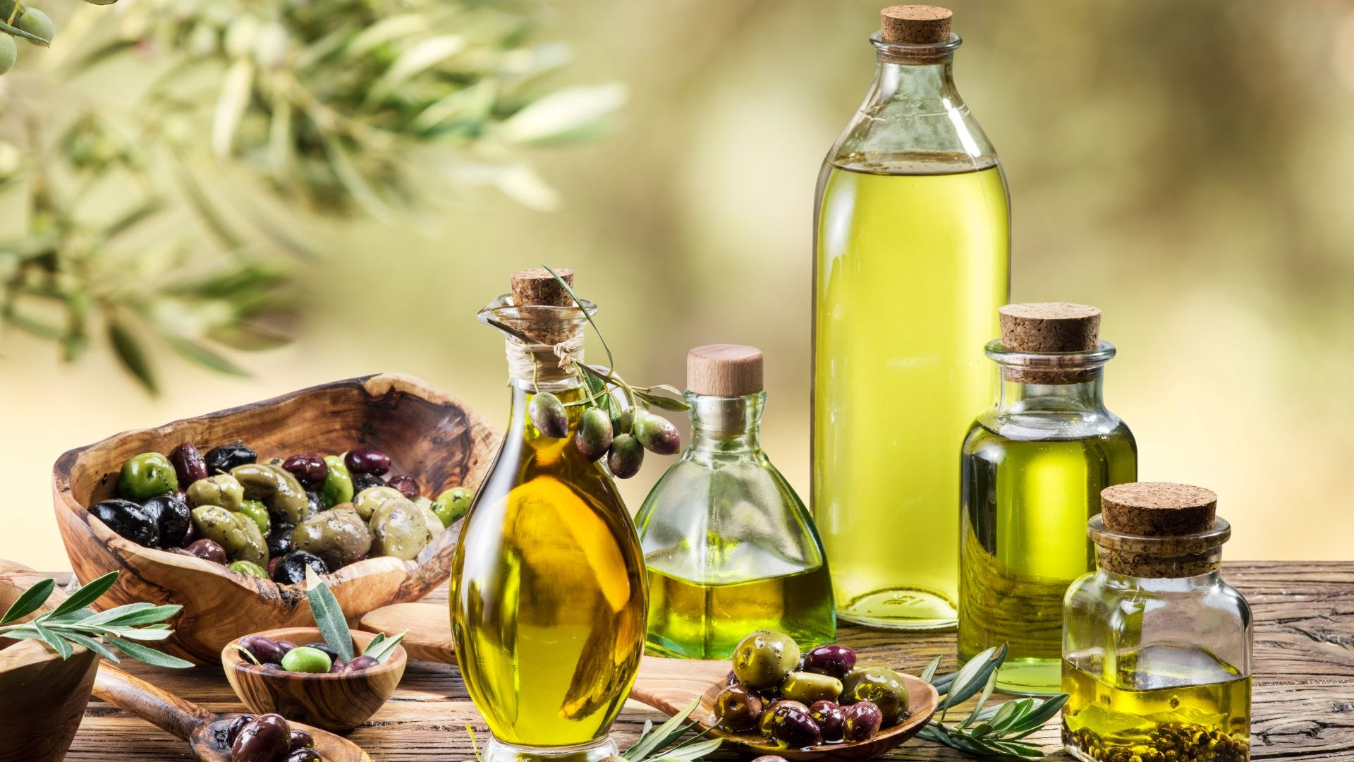 Four bottles of olive oil and olive berries on the wooden table under an olive tree.