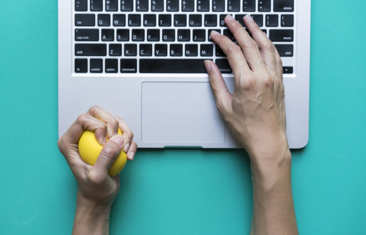 one hand squeezing yellow stress ball while the other types on a laptop