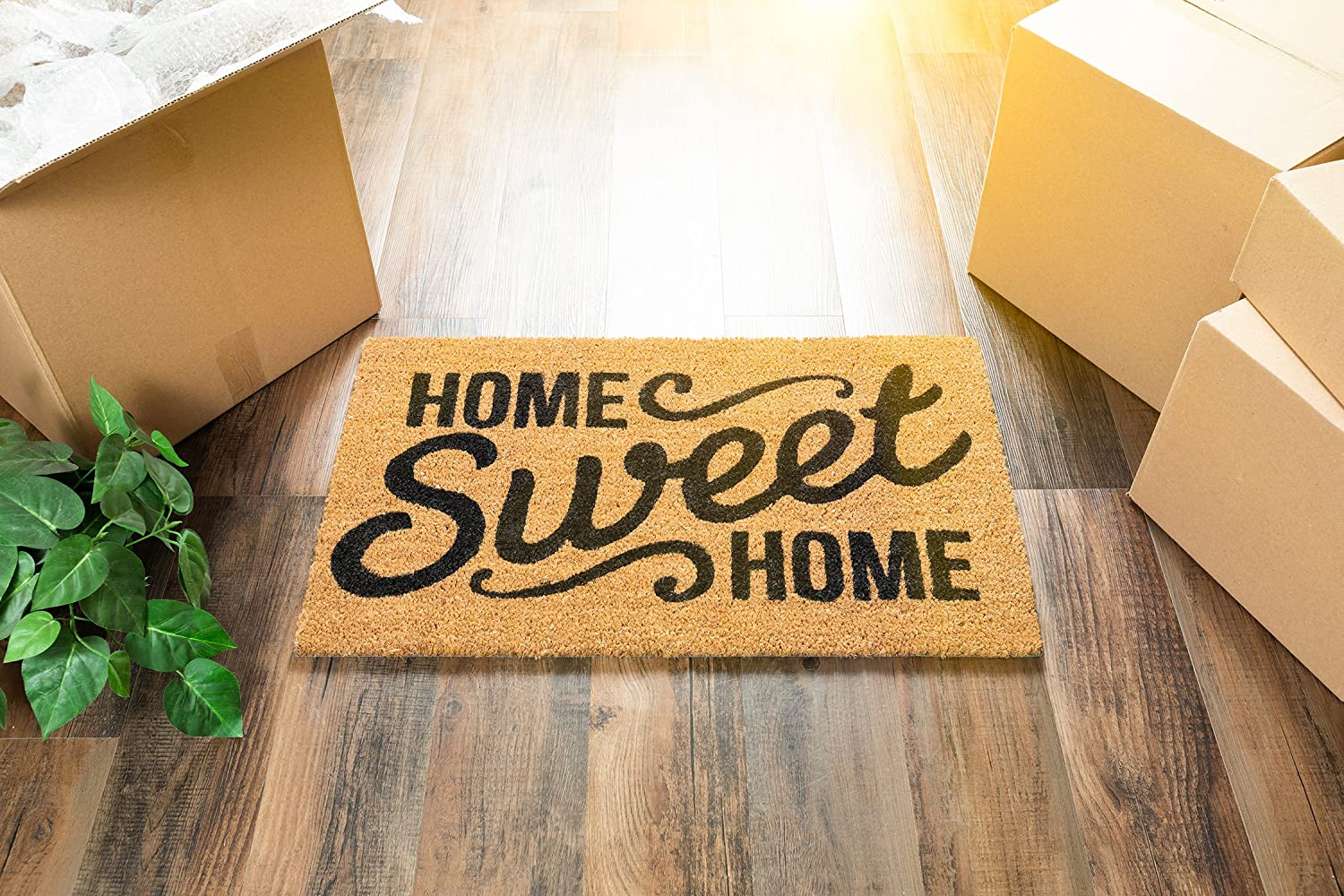 """A doormat reading """"home sweet home"""" sitting next to moving boxes"""