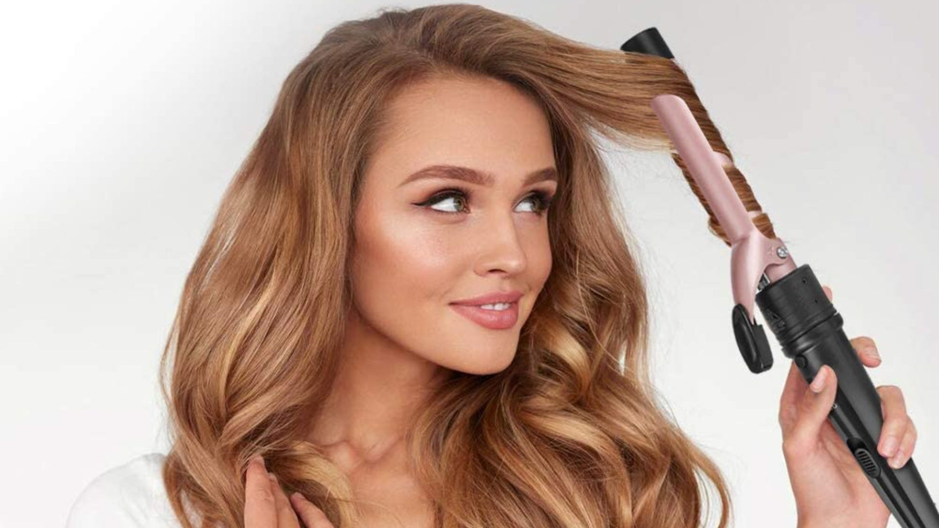 A brunette looks at a pink curling wand as it curls a strand of her hair..
