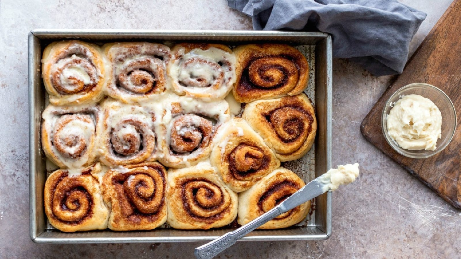 A top view of cinnamon rolls with a maple frosting being smeared over each soft warm bun.