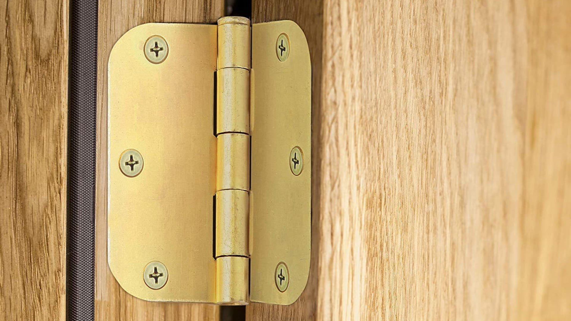 A satin brass hinge installed on a wooden door.