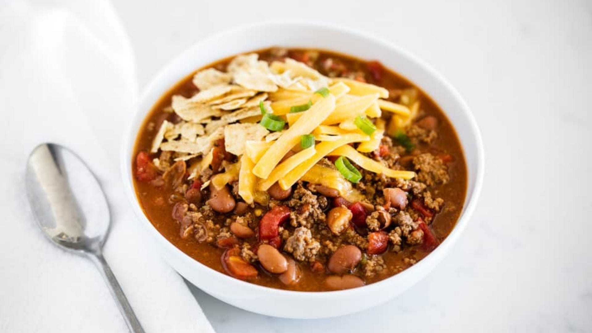 A bowl of chili with cheese on top.