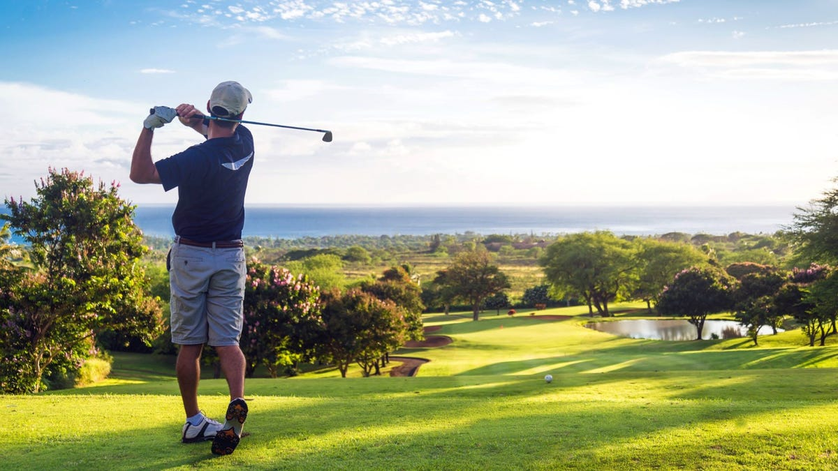 A man swinging a golf club on a green course.