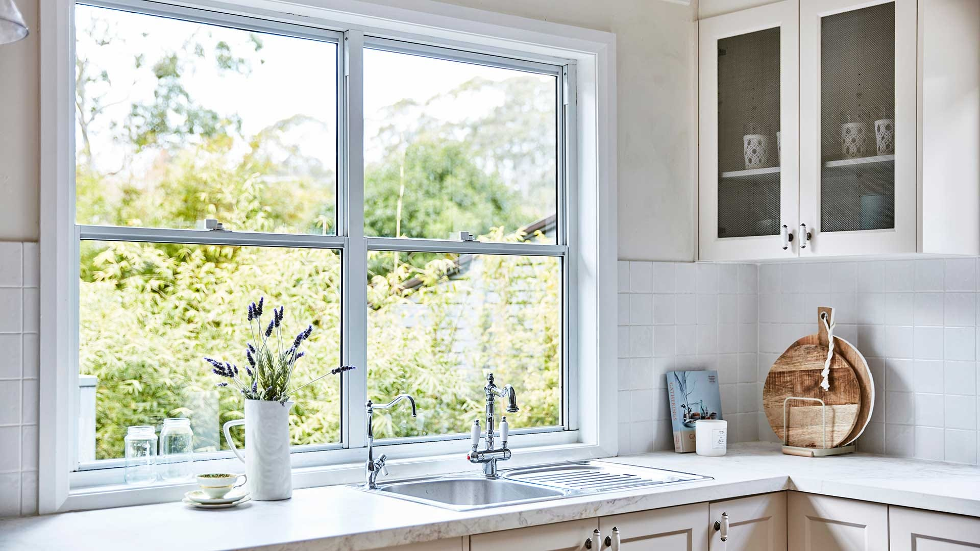 A sunny kitchen with a stainless steel sink under a large window.