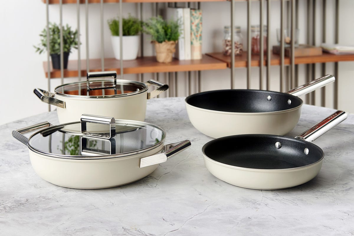 The new Smeg frying pans, saucepan, casserole dish, and wok sitting on a white marble countertop.