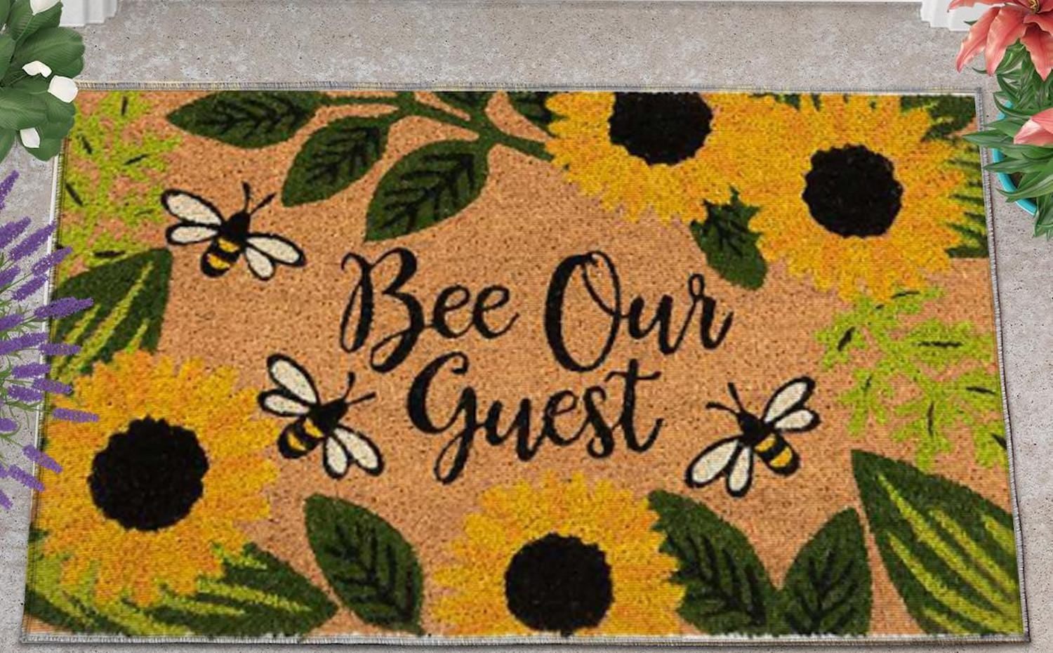 """A doormat with sunflower and bee designs surrounding """"bee our guest"""" in script"""