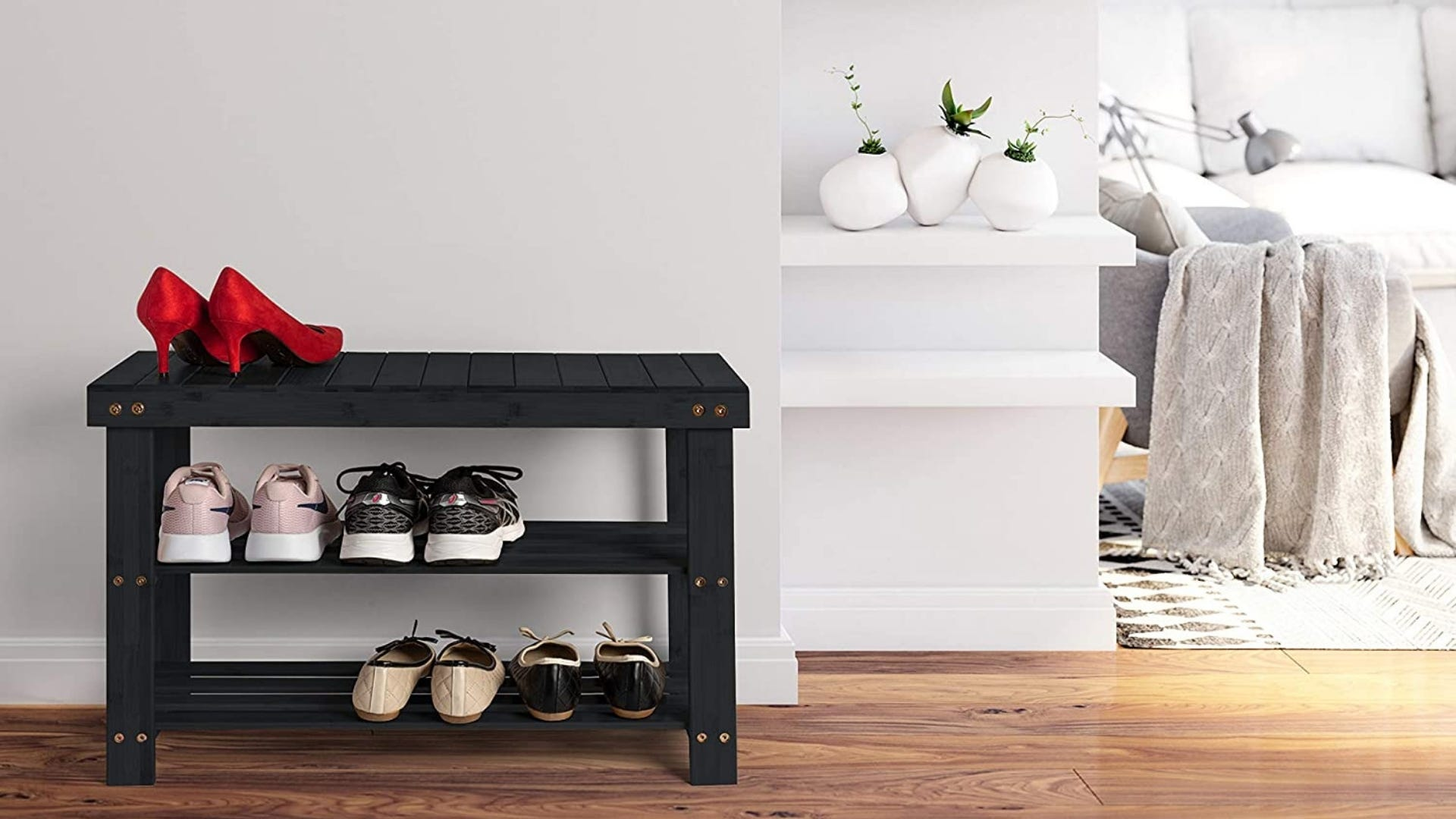 Black shoe rack with three levels holding five pairs of shoes.