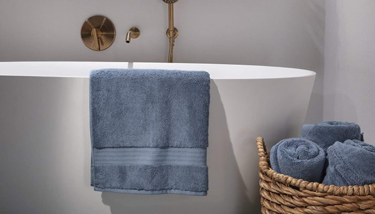 blue-gray towel slung over the side of a white tub beside a wicker basket of matching towels