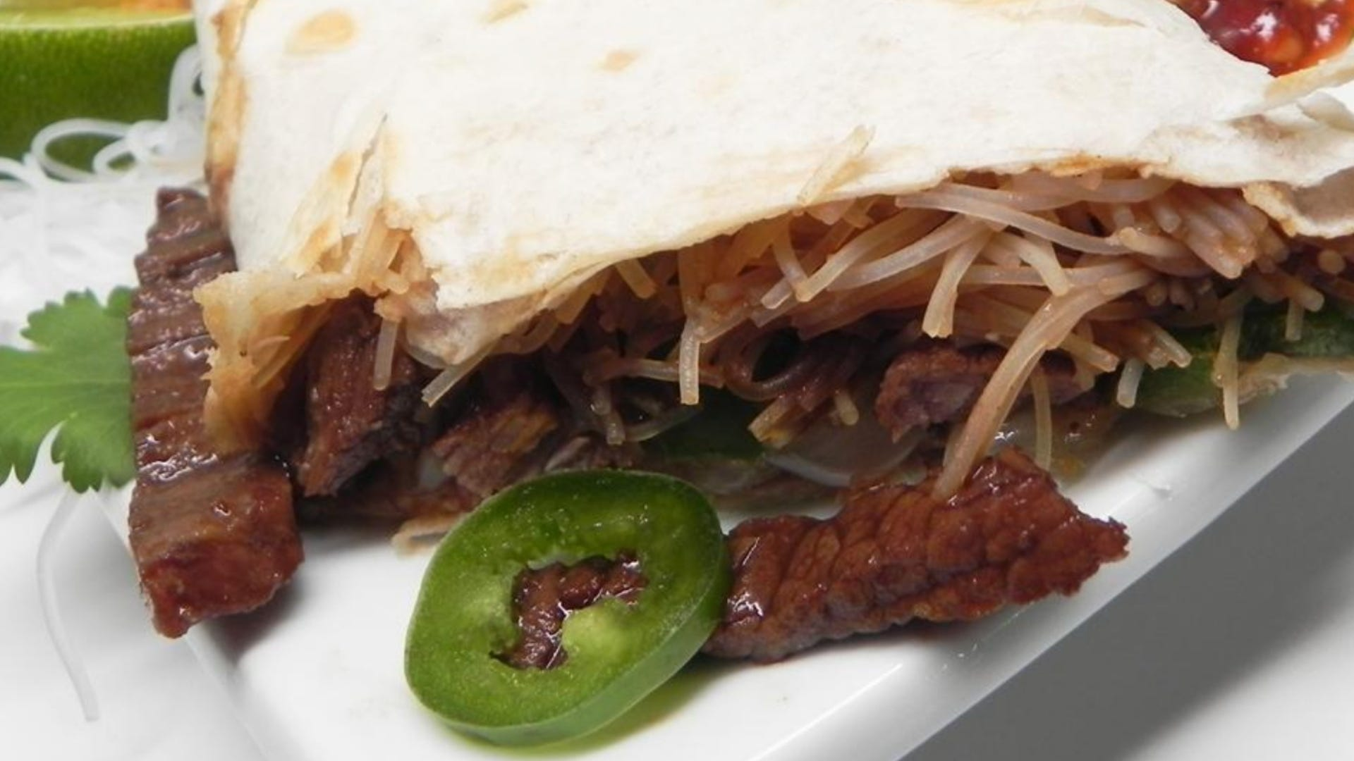 Burrito filled with rice noodles, beef, and jalapeños