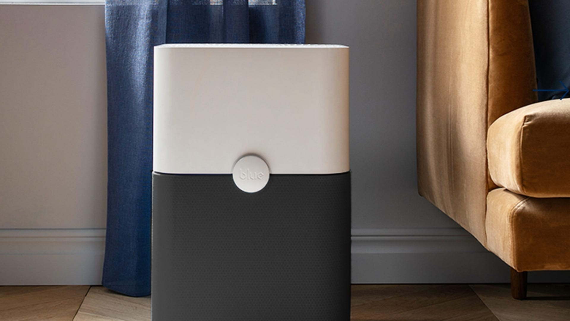The Blueair Blue Pure 211+ Air Purifier on the floor in a living room.