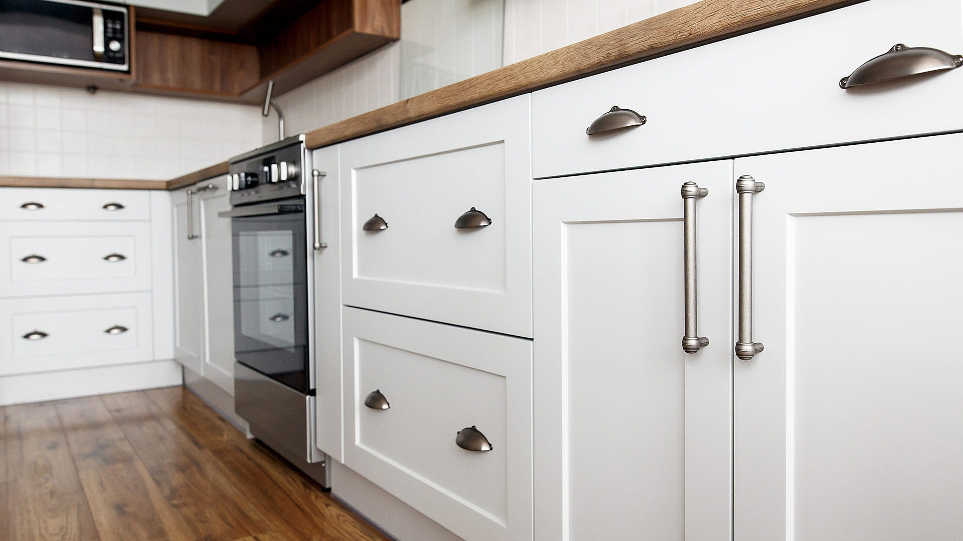 White kitchen cabinets in a kitchen with oak counters and a white tile backsplash.