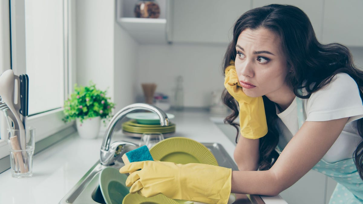 A woman at a kitchen sink full of dishes, looking out the window.