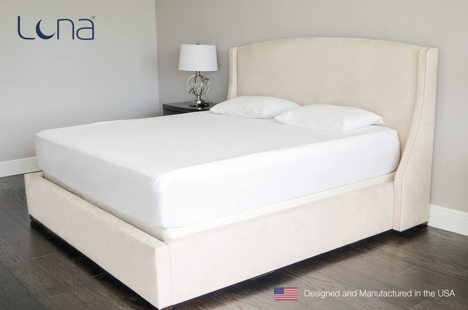 A bare bed outfitted with a Luna brand mattress and pillow protector.
