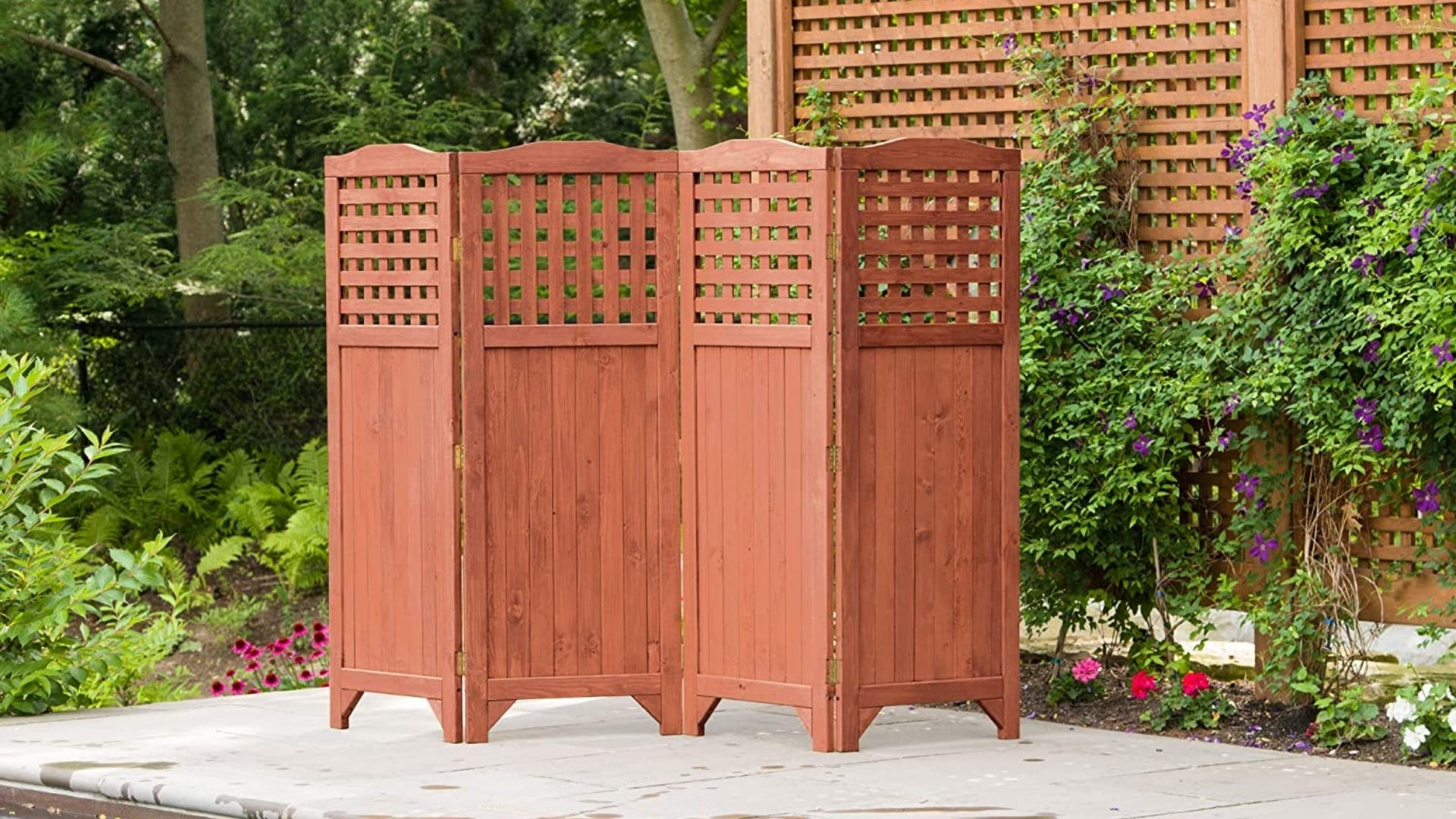 A brown free standing screen divider sits on a porch.