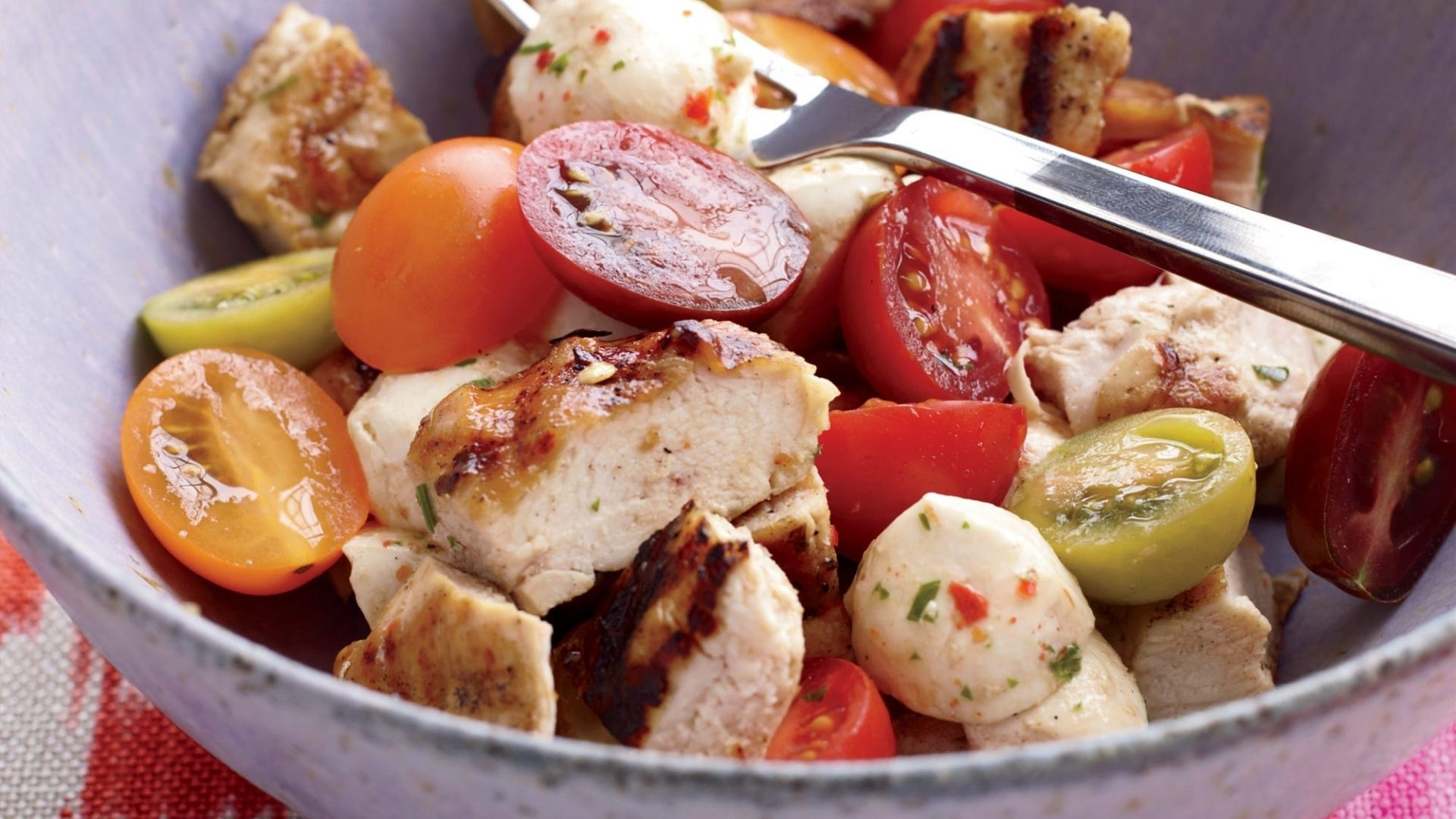 A bowl filled with grilled chicken, tomatoes, and mozzarella cheese balls.