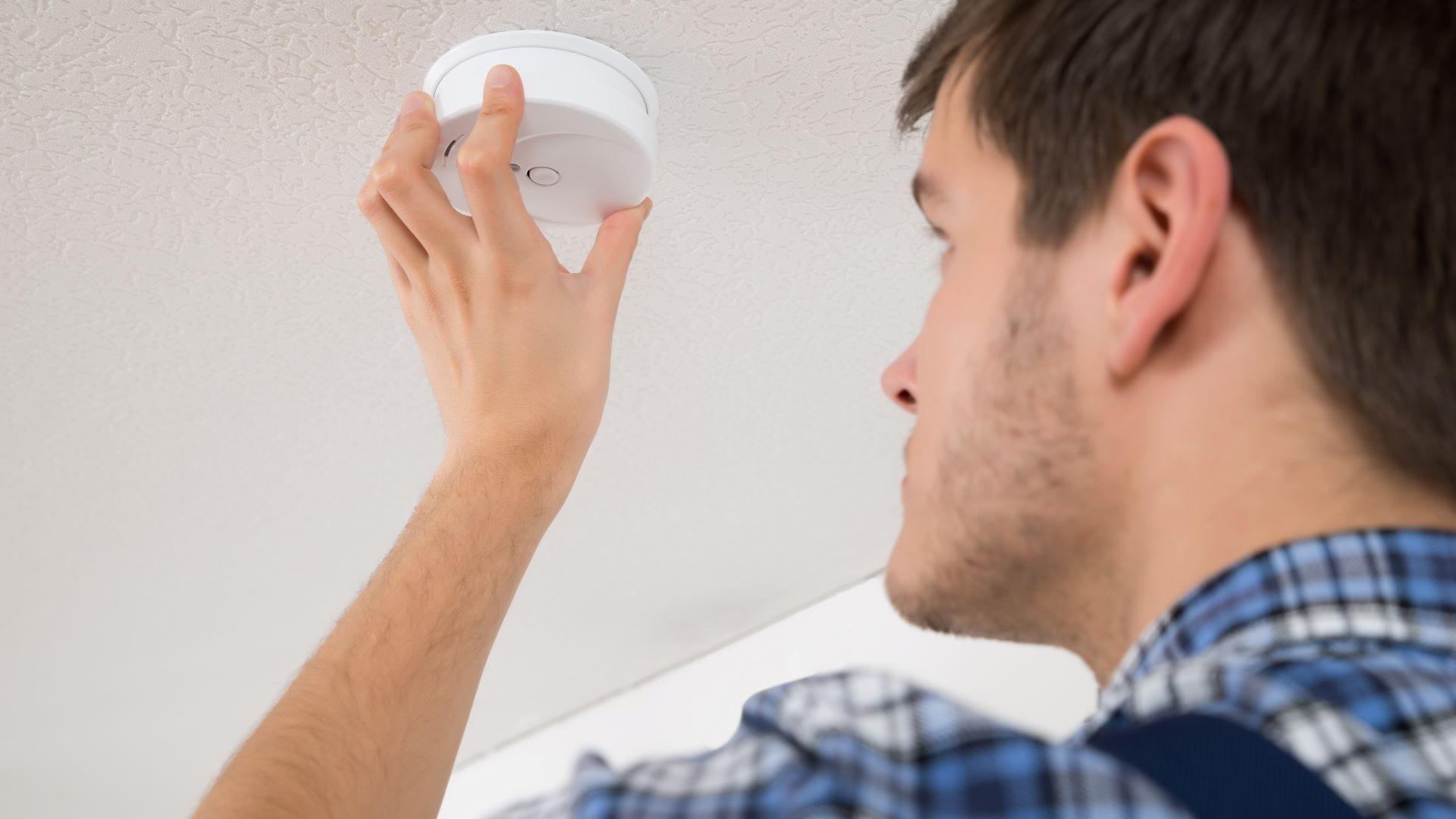 A man checking a smoke detector.
