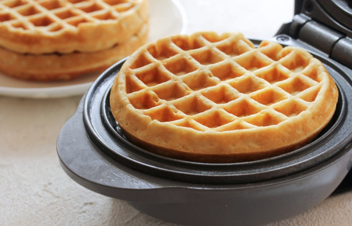 a freshly made round waffle in a waffle maker