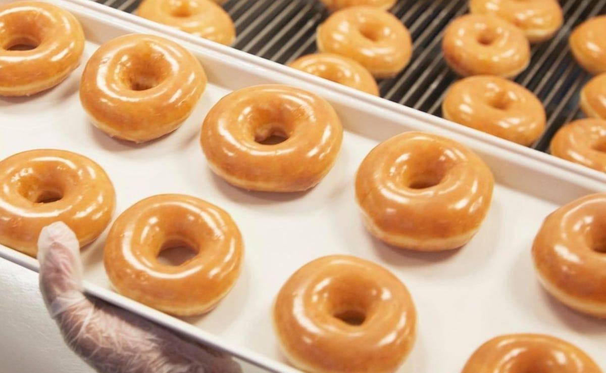 Someone holding a tray of freshly glazed Krispy Kreme doughnuts.