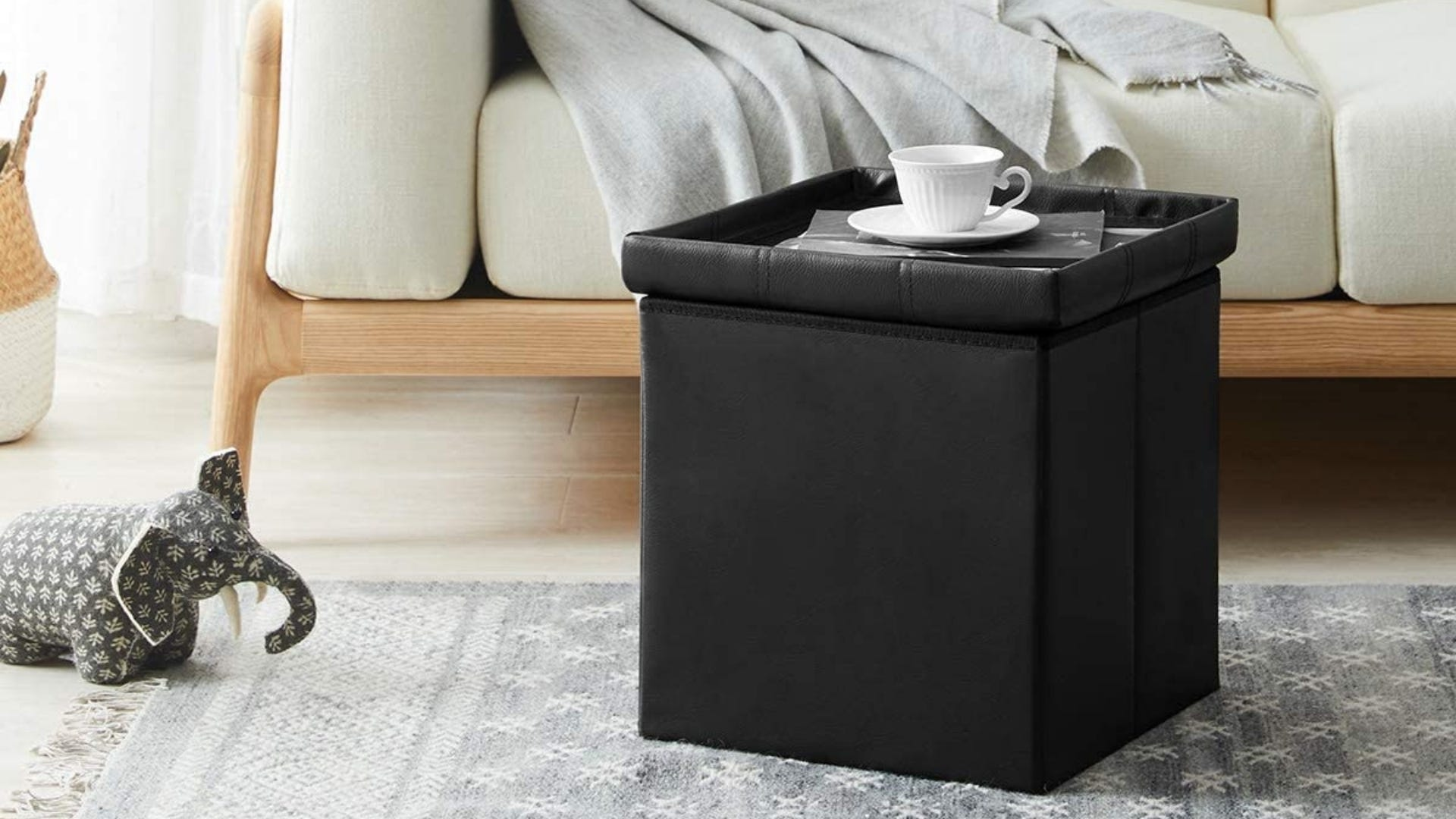 A black storage ottoman with a teacup and saucer on top.