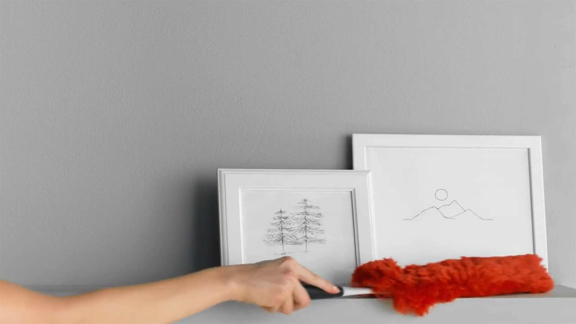 A person dusting a ledge and picture frames using a bright red microfiber OXO hand duster.