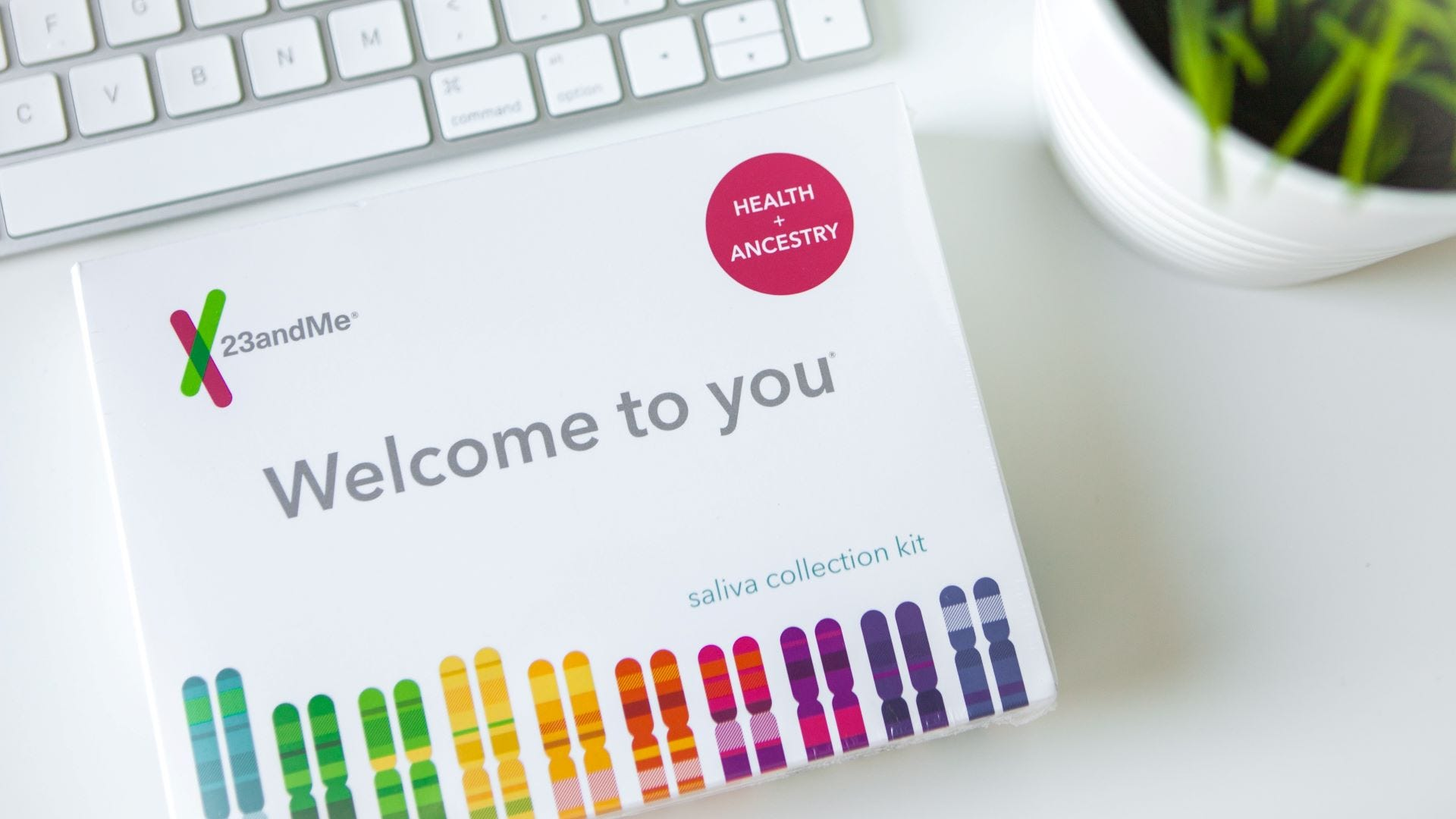 A 23andMe DNA kit sitting next to a laptop.