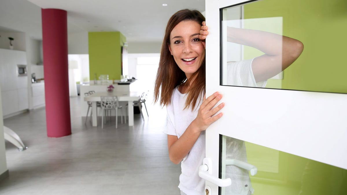 A woman answering the door at home.