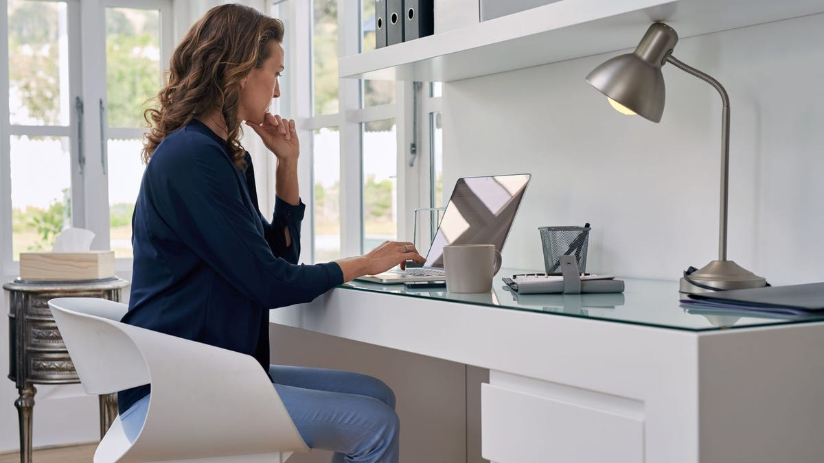 A woman working at a desk in a modern, all-white, home office.