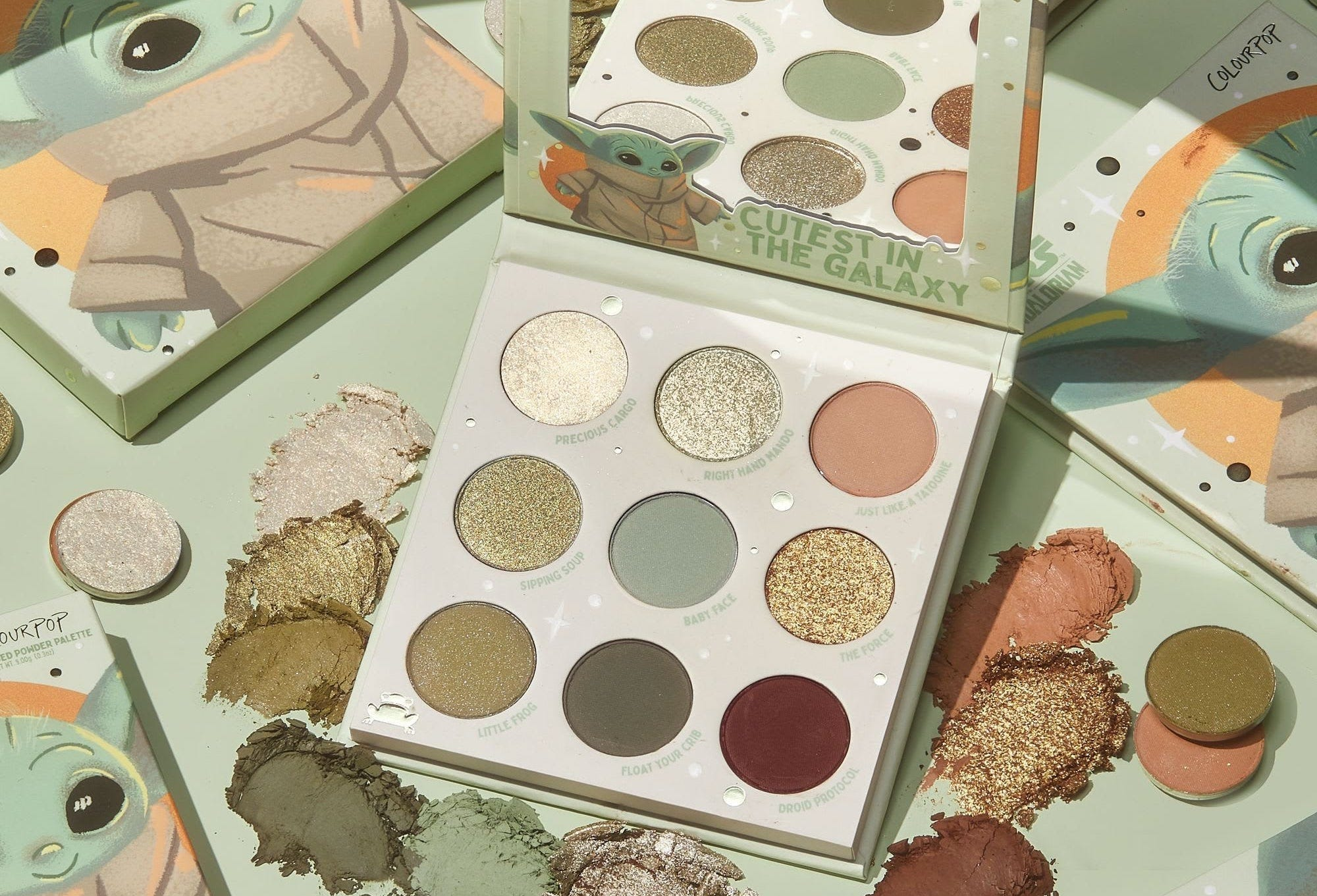 A nine-color eyeshadow palette in greens and golds, surrounded by images of Baby Yoda and piles of eyeshadow powder