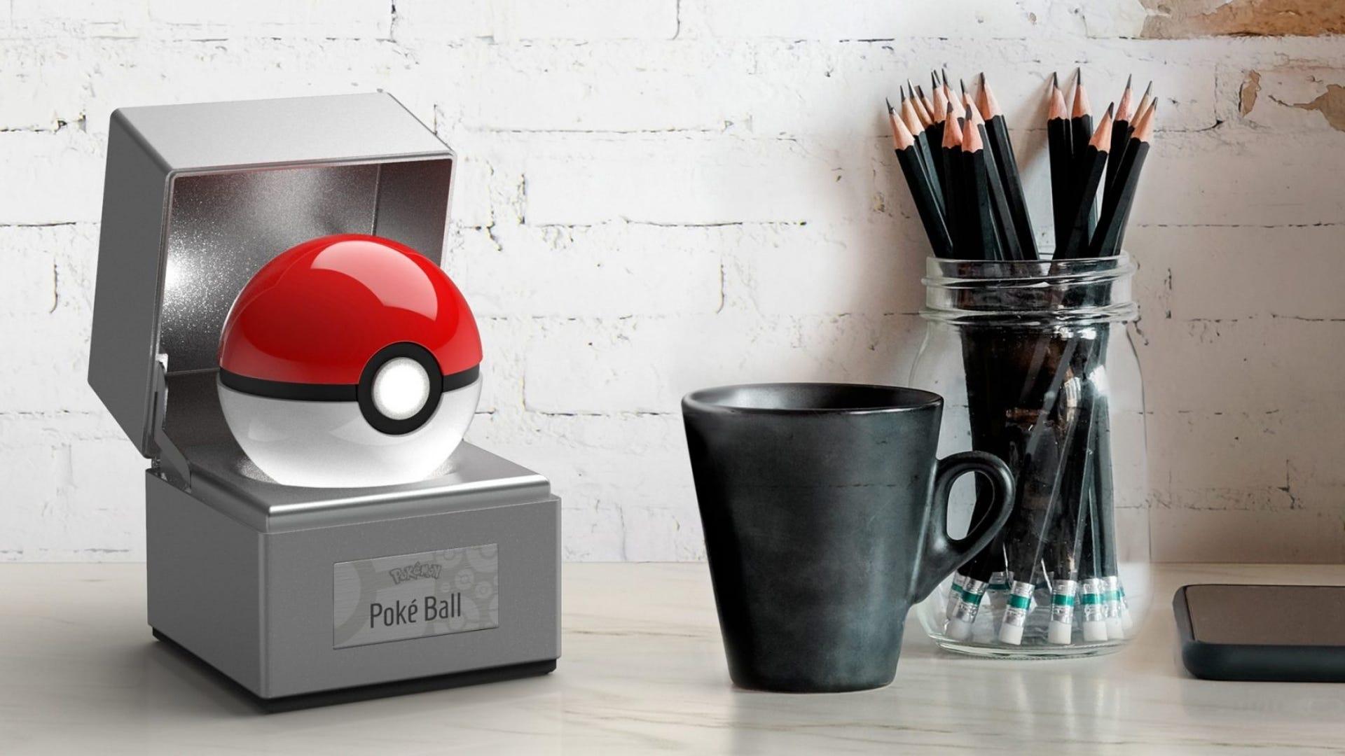 A Poke Ball replica sits on a table next to a mug and pencils.