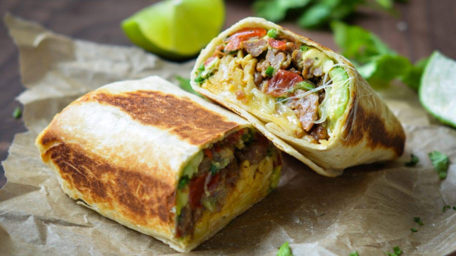 A breakfast burrito filled with scrambled eggs, peppers, avocado and sausage, cut in half served on parchment paper with fresh cilantro and lime.