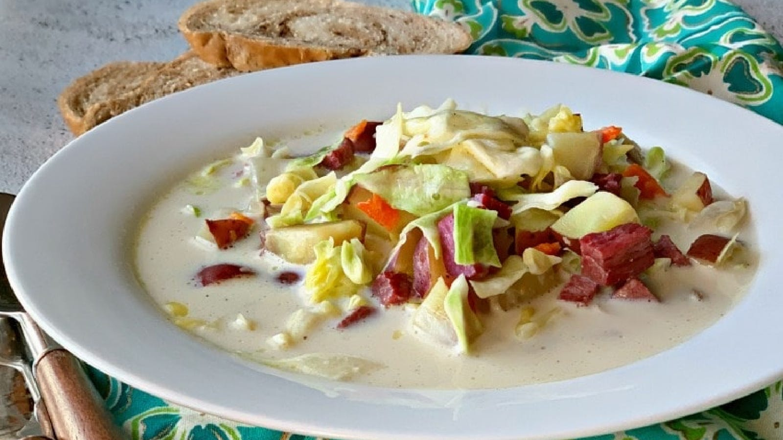 Creamy corned beef and cabbage soup filled in a shallow bowl with bread and a spoon along side of the bowl.